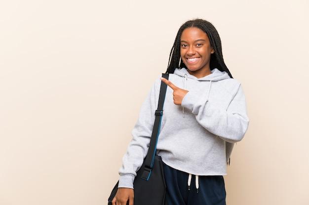 Afroamerikanersport-jugendlichmädchen mit dem langen umsponnenen haar zeigend auf die seite, um ein produkt darzustellen