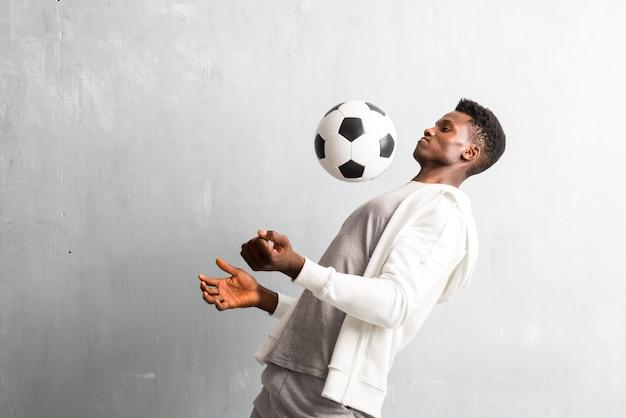 Afroamerikanersportler, der eine fußballkugel anhält
