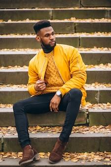 Afroamerikanerstudent, der auf treppen im park sitzt