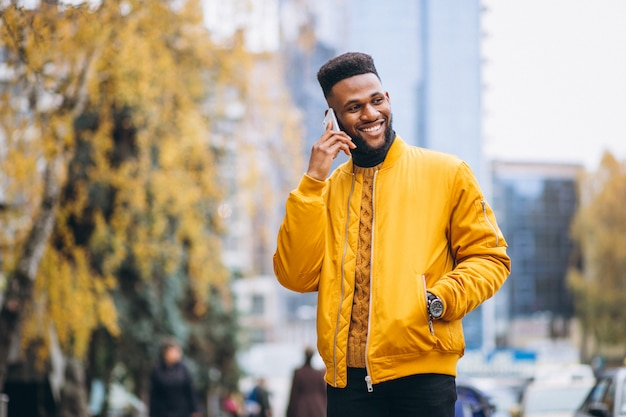 Afroamerikanerstudent, der in die straße geht und am telefon spricht