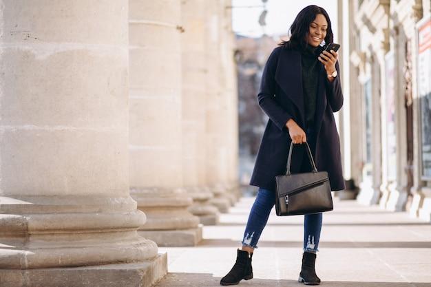 Afroamerikanerstudentenmädchen mit telefon durch die universität