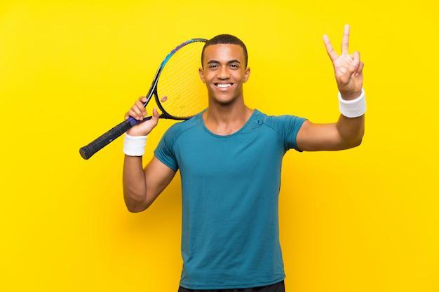 Afroamerikanertennisspielermann, der siegeszeichen lächelt und zeigt