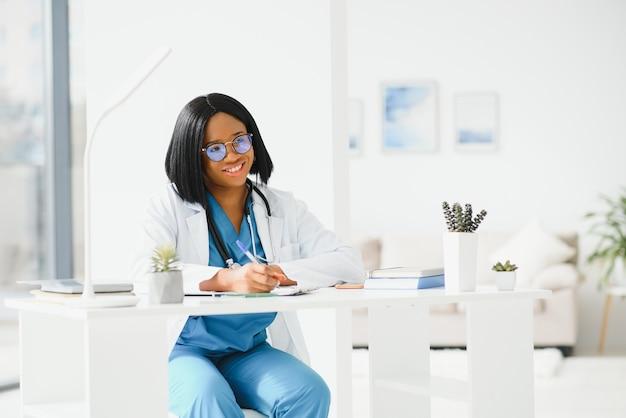 Afroamerikanische ärztin, die in ihrem büro in der klinik arbeitet
