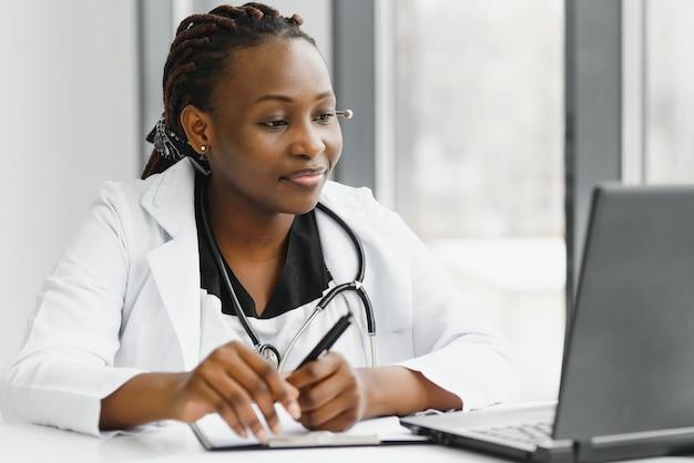 Afroamerikanische ärztin, die in ihrem büro online unter verwendung des tragbaren informationsgeräts arbeitet.