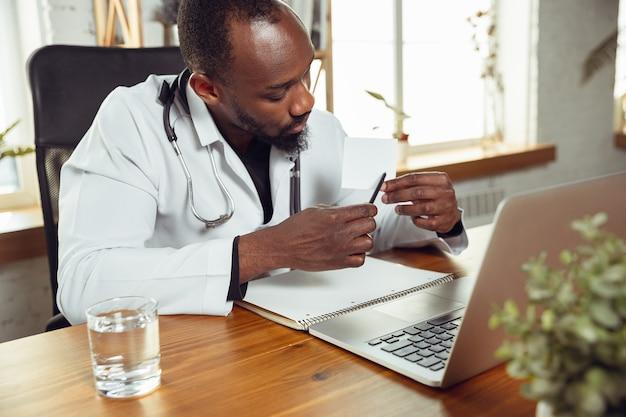 Afroamerikanische arztberatung für patienten, die im kabinett arbeiten, nahaufnahme