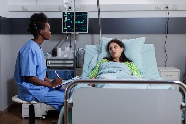 Afroamerikanische assistentin überwacht kranke frau, die über krankheitssymptome diskutiert