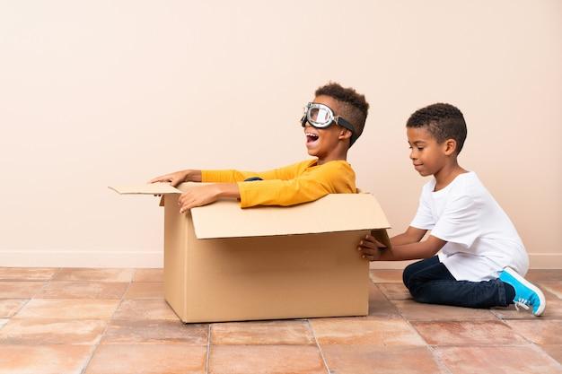 Afroamerikanische brüder spielen. junge in einer pappschachtel mit fliegerbrille