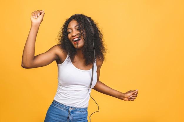 Afroamerikanische dame, die musik hört und mit geschlossenen augen tanzt