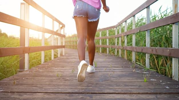 Afroamerikanische dame mit langen, schlanken beinen in blauen shorts und heller bluse läuft entlang einer holzbrücke zwischen feldern rückansicht