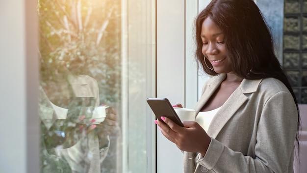 Afroamerikanische dame trinkt kaffee und sms am telefon
