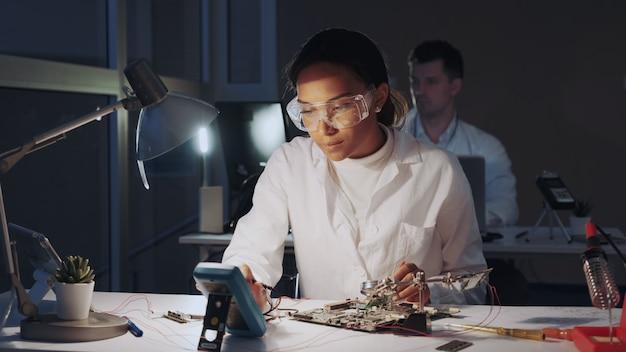 Afroamerikanische elektronikingenieure überprüfen das motherboard mit einem multimetertester und anderen elektronischen geräten im labor