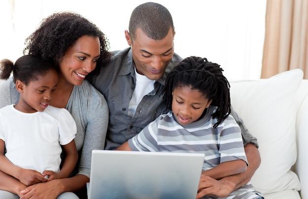 Afroamerikanische familie, die einen laptop auf dem sofa verwendet