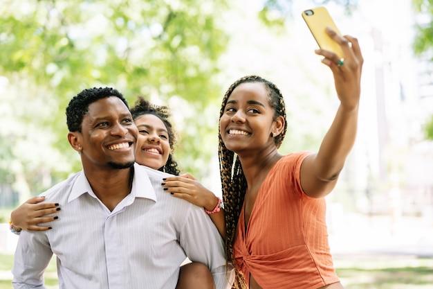 Afroamerikanische familie, die spaß hat und einen tag im park genießt, während sie zusammen mit einem mobiltelefon ein selfie macht.