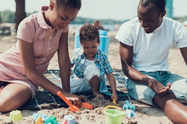 Afroamerikanische familie ruht sich am river beach aus