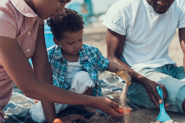 Afroamerikanische familie ruht sich am strand aus
