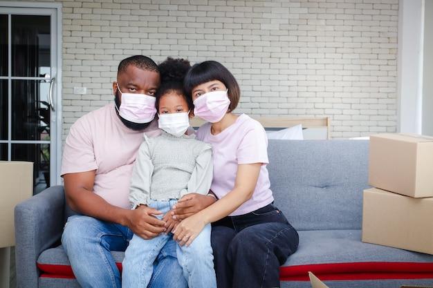 Afroamerikanische familie zieht in ein neues zuhause und sitzt auf dem sofa im wohnzimmer in