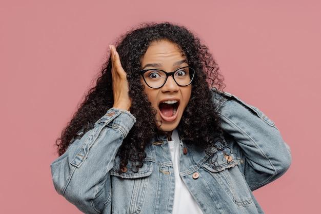 Afroamerikanische frau deckt die ohren, schreit laut, ignoriert laute geräusche, hält den mund weit offen