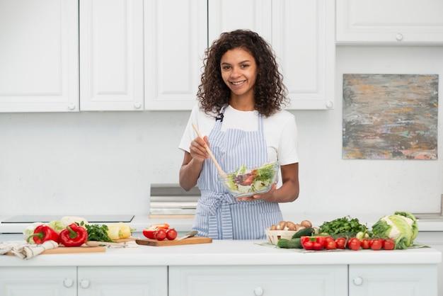 Afroamerikanische frau der vorderansicht, die salat zubereitet
