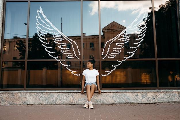 Afroamerikanische frau, die an der glasvitrine mit engelsflügeln sitzt