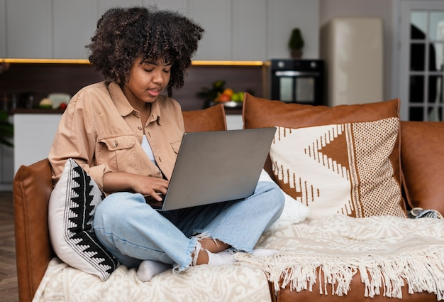 Afroamerikanische frau, die an laptop arbeitet
