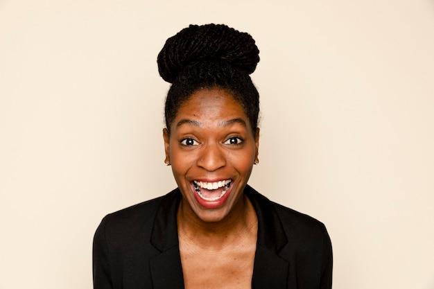 Afroamerikanische frau, die auf beigefarbenem hintergrund lächelt