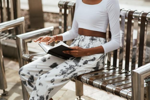 Afroamerikanische frau, die auf einer bank sitzt und ein buch liest
