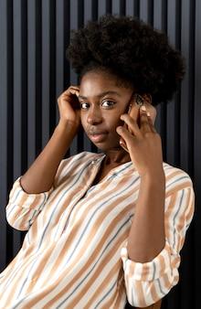 Afroamerikanische frau, die mit jemandem auf ihrem smartphone spricht