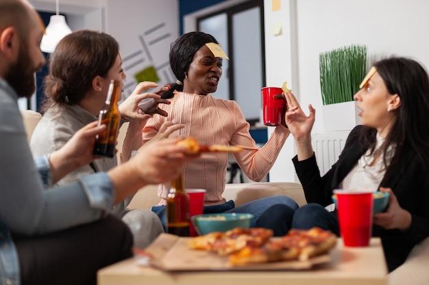 Afroamerikanische frau, die nach der arbeit im büro ein ratespiel mit freunden spielt. multiethnische gruppe von arbeitern vermutet nachahmung für lustige fröhliche aktivitäten beim essen und trinken von bier