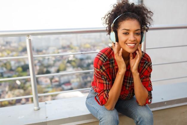 Afroamerikanische frau, die reizende musik durch kopfhörer genießt, gekleidet in kariertes hemd, stehend auf dach. hintergrund der stadtlandschaft.
