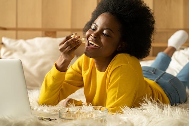 Afroamerikanische frau, die sich entspannt, popcorn isst, film auf laptop sieht, im bett liegend