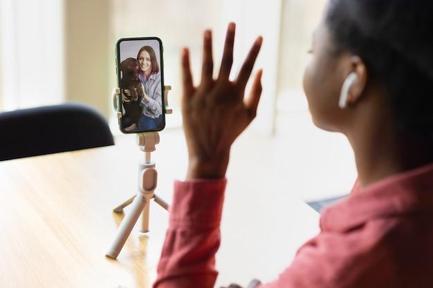 Afroamerikanische frau, die von ihrem smartphone aus video-chats oder live-streaming ansieht