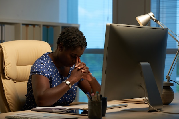 Afroamerikanische frau, die vor computer im büro sitzt und kopf auf gefalteten händen lehnt