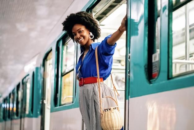 Afroamerikanische frau hängt an einer zugtür