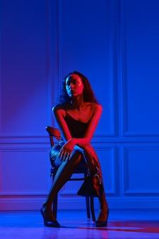 Afroamerikanische frau im kleinen kleid, netzstrumpfhose sitzt auf stuhl mit handtasche unter neonlicht