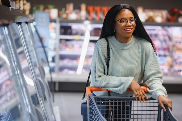 Afroamerikanische frau mit einkaufswagen im supermarkt.