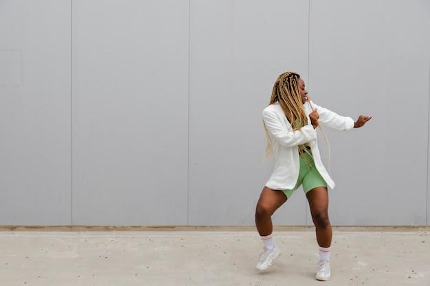 Afroamerikanische frau mit langen blonden zöpfen tanzt auf der straße textfreiraum urban dancing