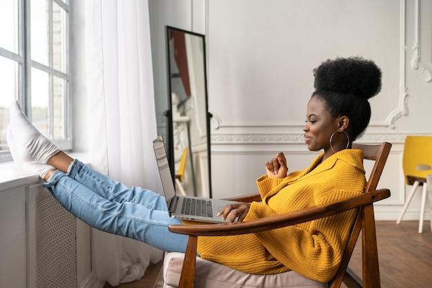 Afroamerikanische frau sitzt auf stuhl, beine auf fensterbank gelehnt, im video-chat sprechend