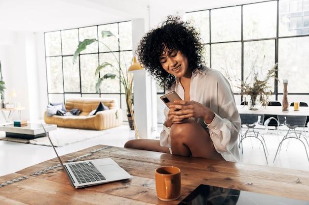 Afroamerikanische frau sms auf handy in loft-wohnung küche home technology copy space