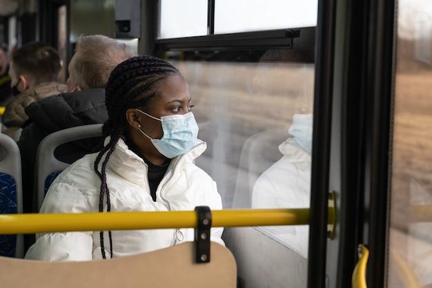 Afroamerikanische frau trägt medizinische maske reisen im bus des öffentlichen verkehrs in der neuen normalität von covid