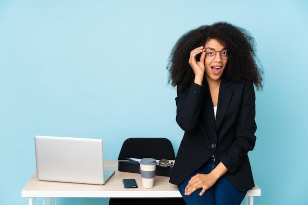 Afroamerikanische geschäftsfrau, die an ihrem arbeitsplatz mit brille arbeitet und überrascht