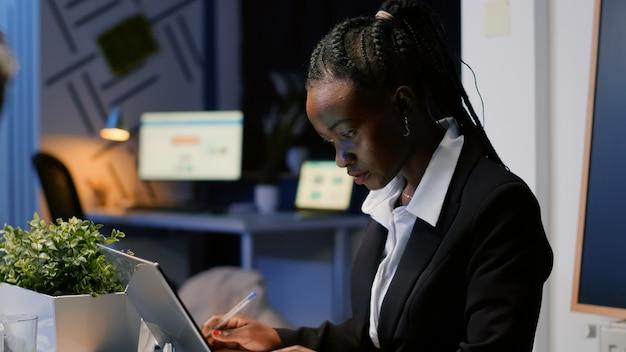 Afroamerikanische geschäftsfrau, die unternehmensstatistiken auf notebook schreibt, während multiethnische teamarbeit die managementpräsentation im bürokonferenzraum diskutiert. diverse geschäftsleute, brainstorming-ideen