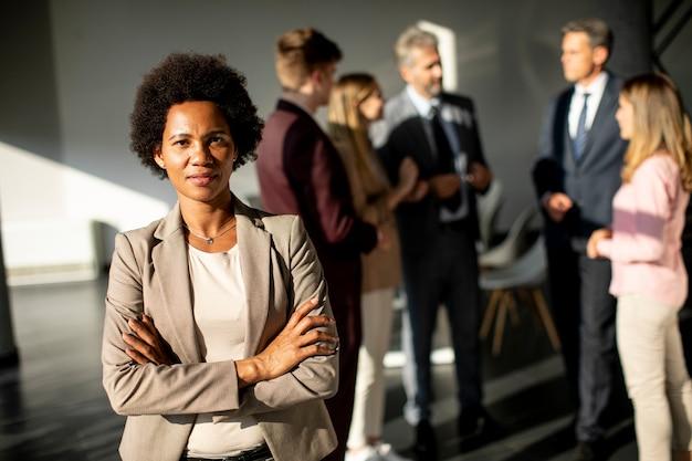 Afroamerikanische geschäftsfrau, die vor ihrem team im büro steht