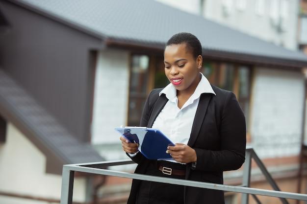 Afroamerikanische geschäftsfrau in bürokleidung lächelnd, sieht selbstbewusst und glücklich aus, beschäftigt