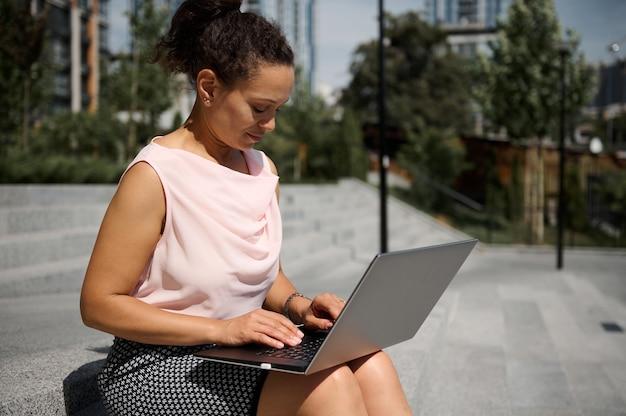 Afroamerikanische geschäftsfrau mittleren alters in legerer kleidung, die auf stufen sitzt und auf urbanem hintergrund am laptop arbeitet