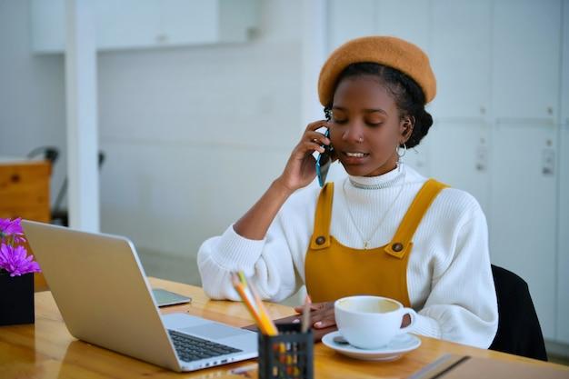 Afroamerikanische geschäftsfrauen rufen im büro handys an - schwarze