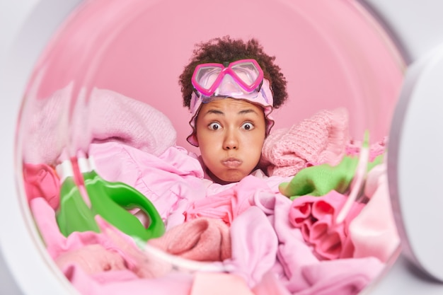 Afroamerikanische haushälterin bläst wangen macht grimasse hat überraschten ausdruck trägt schnorchelmaske auf der stirn, umgeben von schmutziger wäsche und waschmittel-posen in der waschmaschine
