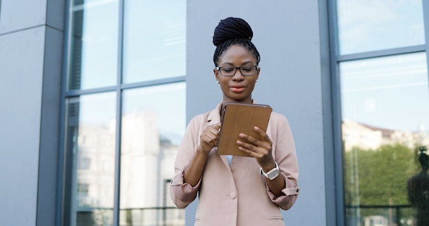 Afroamerikanische junge geschäftsfrau in den gläsern, die auf tablet-gerät tippen und scrollen. frau sms auf computer im freien. selbstbewusste frau mit gadget und chat.