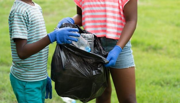 Afroamerikanische kinder, die freiwillig plastikflaschen in einem schwarzen müllsack im park aufheben, helfen müllsammel-wohltätigkeitsumgebung
