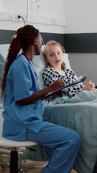 Afroamerikanische kinderkrankenschwester, die krankheitssymptome mit einem kranken kleinen kind bespricht