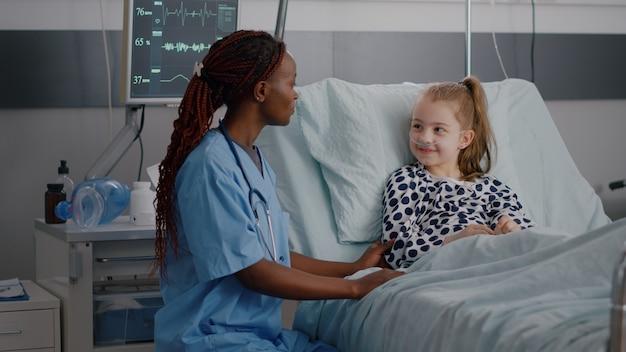 Afroamerikanische kinderkrankenschwester, die neben einem kranken kind sitzt und hoch fünf bespricht, während der genesungsuntersuchung in der krankenstation über die medizinische behandlung diskutiert wird. kleines kind, das eine medizinoperation erleidet